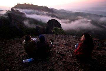 Wisatawan menikmati matahari terbit di puncak Gunung Purba, Nglanggeran, Patuk, Gunung Kidul, Yogyakarta
