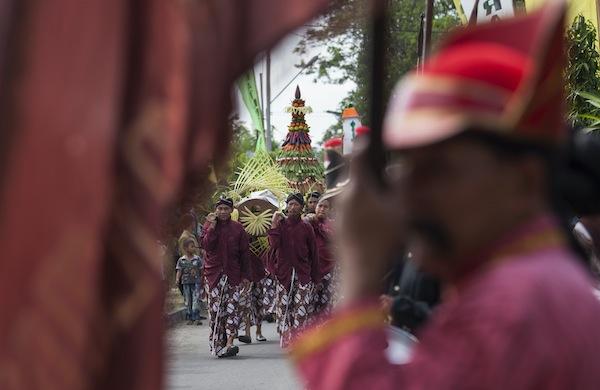 Sejumlah warga dengan pakaian Jawa mengarak gunungan yang berisi hasil bumi dalam tradisi Sadranan Agung Wotgaleh di Berbah, Sleman, Yogyakarta, Sabtu (29/6). Tradisi tersebut bertujuan untuk menghormati para leluhur sekaligus sebagai ungkapan rasa syukur kepada Tuhan Yang Maha Esa menjelang datangnya bulan suci Ramadhan. ANTARA FOTO/Sigid Kurniawan/ss/ama/13