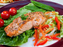 Weight loss Healthy food Delicious blackened salmon served on a bet of lettus with other garnishes