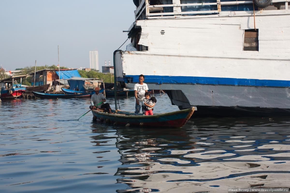 Жители посёлка на воде на лодке переправляются в порт.