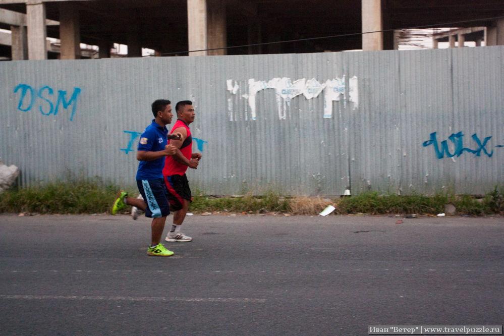 Бегуны тренируются на обочине шоссе