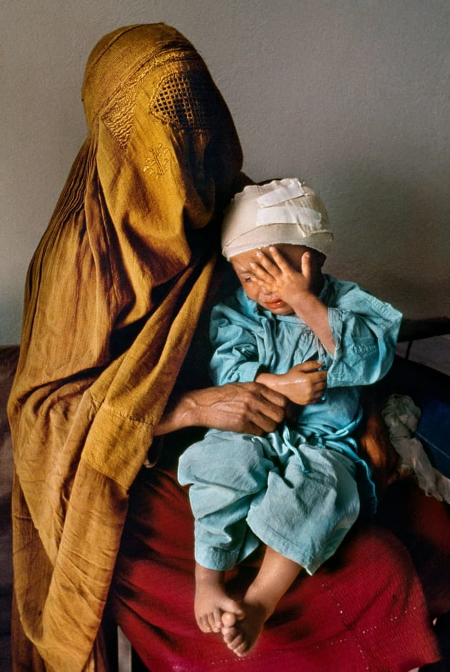 Kabul, 1992. A mother holds her two-year-old son, who was grazed by a stray bullet, at Karte Seh surgical hospital.