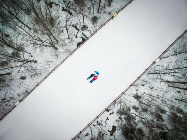 """Dronie by Manish Mamtani. A bridge caked in snow in New Hampshire was the perfect opportunity for Manish Mamtani and his wife, both wearing bright clothing, to create a contrasting """"dronie"""" (selfie taken by drone) against the monotonous white winter cold."""