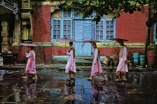 Procession of Nuns, Rangoon, Burma, 1994. Pictures can offer themselves up to you – but only if you have patience. McCurry asked these nuns if he could follow them on their daily walk around the city. He trailed them for several days until, with rain falling and a brightly coloured building as a fitting backdrop, he captured this graceful image. Copyright Steve McCurry.