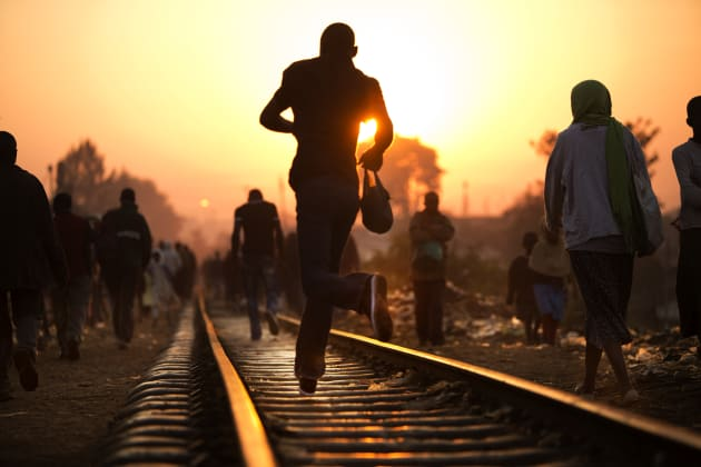 A man rushes along the tracks during the morning commute. Many Kiberans go to jobs at a nearby factory that pays about a $1 a day. © Deanne Fitzmaurice.