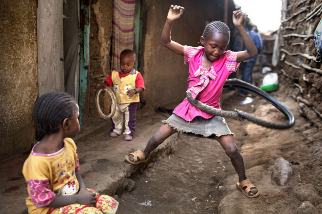 A resourceful young girl uses an old tyre as a Hula Hoop in the slum of Kibera, Kenya - the largest slum in Africa. Only 8% of girls in Kibera ever have the chance to go to school. © Deanne Fitzmaurice.
