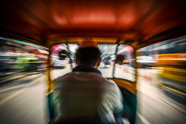 An auto rickshaw driver speeds down the street in New Delhi, India. I shot this image from the backseat with a slow shutter to achieve the zoomed effect for a sense of motion. Canon EOS 6D, 16-35mm f/2.8 lens @ 16mm, 1/40s @ f14, ISO 160, handheld. Contrast, curves and levels adjustment, sharpening in Photoshop CC. Photo © Drew Hopper.