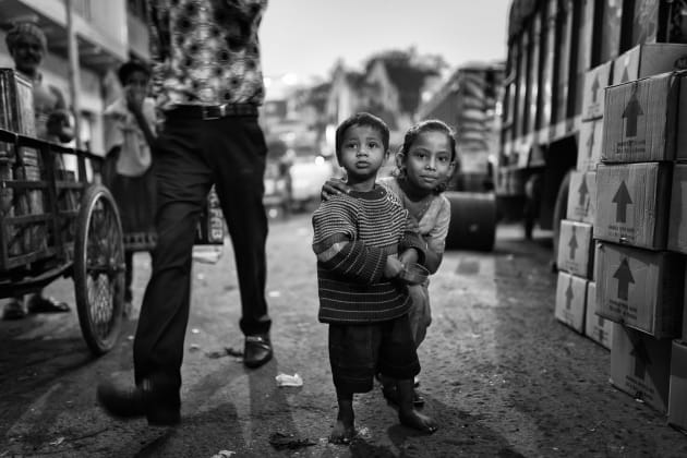 Two young children intrigued by my camera as i walk through a bustling street in kolkata
