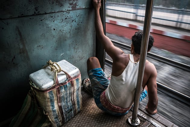 Worker on his way home on the locals' train in Kolkata, India. I slowed my shutter speed down enough to blur the tracks through the doorway while focusing on the man for a sharp visual. Fujifilm X-E2, 18-55mm lens @ 18mm, 1/20s @ f11, ISO 200, handheld. Contrast, curves and levels adjustment, sharpening in Photoshop CC. Photo © Drew Hopper.
