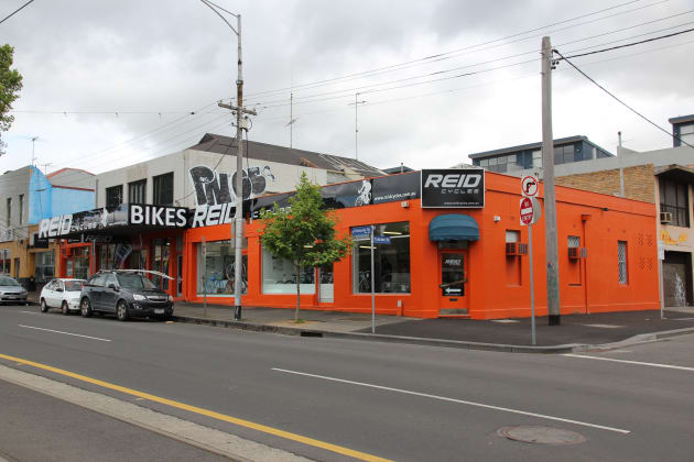 This is Reid Cycles' flagship store in North Melbourne, Vic, photographed not long after they'd expanded into the corner building. After graduation from a suburban garage they started with the small single shop front to the far left of the premises.