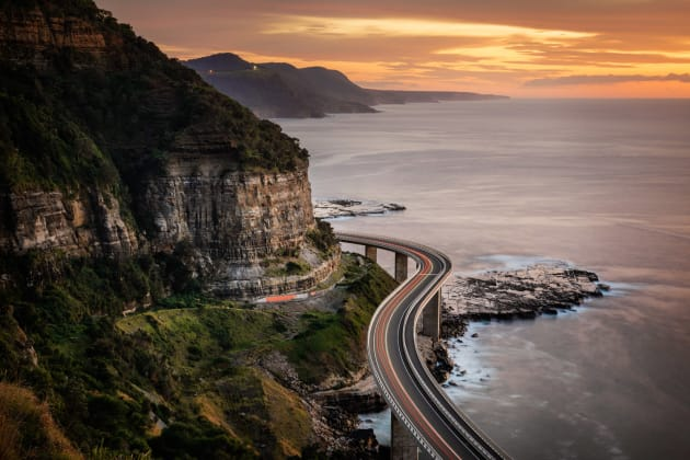 Sea Cliff Bridge, Illawarra, NSW. I had seen this incredible view several times but was really hoping to photograph it with some sky colour. After a very early start I was really excited when the sky lit up as my effort was rewarded. I chose a tighter focal length to focus onto the part of the bridge that turned around the corner. With my long exposure came a car on the bridge, and some great traffic trails as a result. Sony A7R, Canon 24-105mm f/4 @ 55mm, 22 sec at f/11, ISO 100, tripod