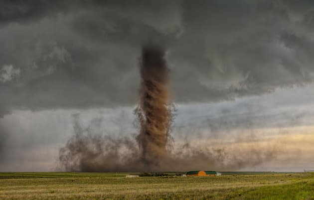 "This shot won James Smart the National Geographic Photo of the Year. A rare and jaw-dropping anti-cyclonic tornado touches down in farmland, narrowly missing a home by a few hundred yards. ""This tornado was fairly slow moving so we had time to get in position for a great shot and see the power in the rotation of the funnel."" Canon EOS 5D Mark II, 70-200mm lens @ 70mm, 1/90sec @f4, ISO 100."