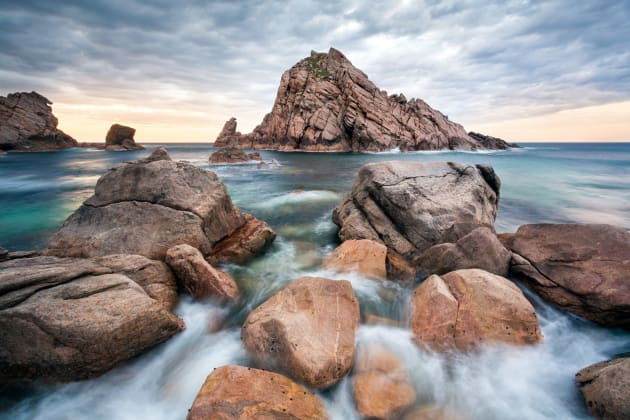 Sugarloaf Rock, South Western Australia. When I arrived at this location I noticed that the seas were quite a lot calmer than on previous visits. I made my way down to the rocky shoreline and noticed the water flowing over the rocks, which I then used as the foreground of my composition. Canon 5D Mark III, Canon 17-40 f/4L, 2 sec @ f/8, tripod