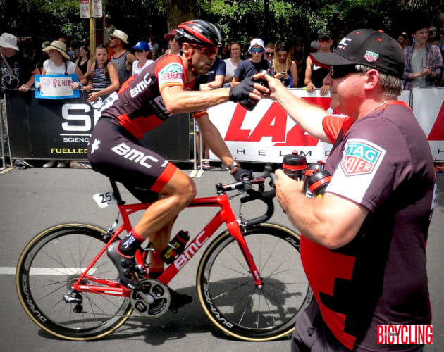 Team BMC 'swannie' Matt hands a bottle to a rider during Stage 6 of the race in Adelaide. Image: Nat Bromhead.