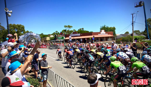 The peloton pass through the quaint village of Willunga prior to starting the famous climb. Image: Nat Bromhead.