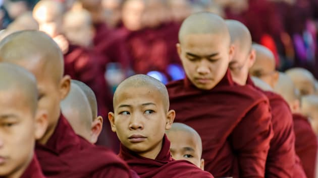 Young Monk rolling his eyes at tourists by Arjan Paauw