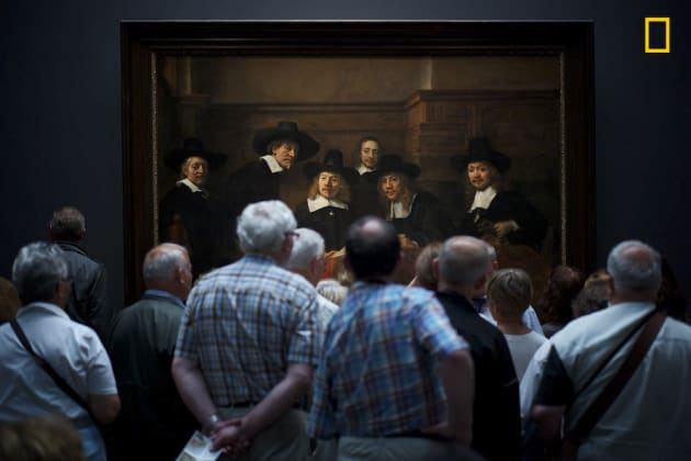 "Photo and caption by Julius Y./National Geographic Travel Photographer of the Year. 2nd Place, People: Interesting moment. Museum visitors curiously watching Rembrandt's painting "" Syndics of the Drapers' Guild"" where it gave the illusion that the people on the paintings too are curiously watching the visitors."