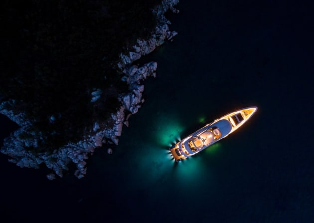 Night lights by jeff. A private superyacht stands out with its lights in the dark waters at night from above.