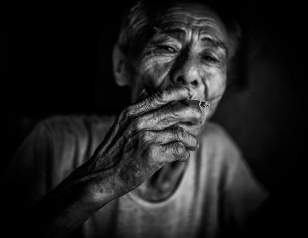 An elderly man smoking a cigarette in his home in Hoi An, Vietnam. Converting from colour to monochrome helped define the wrinkles on his face to create interesting textures. Underexposing the background eliminated any unwanted distractions. Fujfilm X100S, fixed 35mm lens. 1/800s @ f2,  ISO 400. Monochrome conversion, contrast and clarity adjusted in Adobe Lightroom.