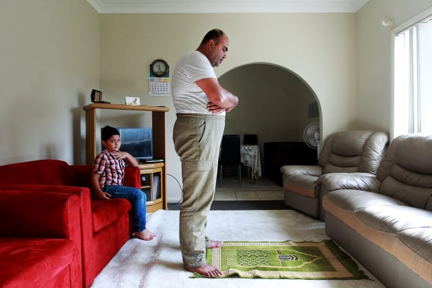 Ahmad looks on as his father Abdullah Tinawi prays in their living room on 16 December, 2015 in Wollongong. The Tinawi family from Al-Zabadani, southwestern Syria have found refuge in Australia following a long and tumultuous journey from their homeland in 2012. © Lisa Maree Williams.