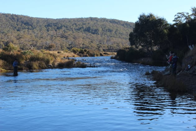 A crowd of anglers fishing a deep pool at the tail-end of some rapids on the Eucumbene River. The popular locations become very crowded during the spawn run.