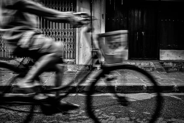 Cyclist riding his bicycle down the street in Yangon City, Myanmar. I anticpated the moment he would pass through my frame while using a slow shutter to add a slight sense of motion blur. Fujifilm X100S, 23mm lens @ 23mm, 1/20s @ f5.6, ISO 400, handheld. Contrast, curves and levels adjustment, sharpening and monochrome conversion in Photoshop CC. Photo © Drew Hopper.