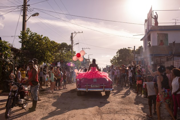 Pura rides around her neighborhood in a pink 1950s convertible, as the community gathers to celebrate her fifteenth birthday, in Havana, Cuba. © Diana Markosian, Magnum Photos