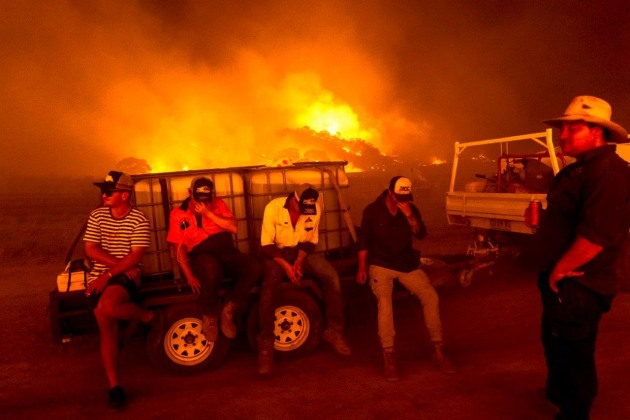 © Daniel Berehulak. Farmers, friends, and neighbours ready their water-laden trucks in order to battle approaching running fires to defend cattle on Bredbo Station, NSW, on 1 February, 2020.