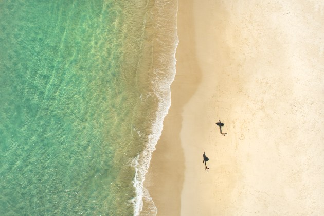 © Craig Parry. Surfers' Shadows. An abstract image of two surfers as their shadows run symmetrical across the sand in Byron Bay. A finalist in 2013 Nikon surf photography competition held in conjunction with Surfing Australia.