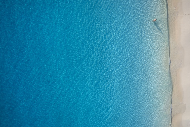 "© Craig Parry. Lost in the Pacific. ""An image of my wife in what seems the middle of nowhere. The use of negative space from above can have its benefits especially a scene like this. The footprints leading into the water and the hues of the blue spectrum make this one of my favourite drone images."""