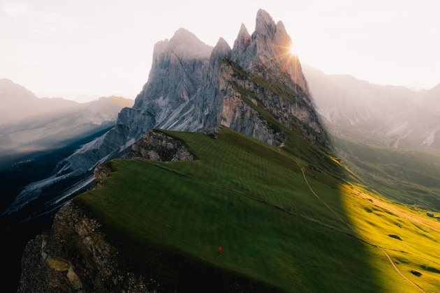 Seceda, Italy. Easily one of the most spectacular rock formations in the world. The leading lines and stark rock to grass contrast draw photographers from all over the world hoping for perfect conditions. I saw this man in red walking down the slope and immediately flew the drone up to a height where the sun would sit as a side reveal. DJI Mavic 2 Pro. 1/240s @ f4, ISO 100. +O.7EV.