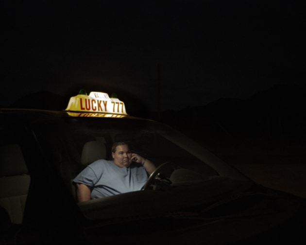 © Juliet Taylor. 1st Place - Portrait Prize. Unlcky. Pioneertown sits in the basin of the San Bernardino High Desert, where is is so black at night you can barely see a foot in front of you. Sheryl sits in her taxi outside Pappy & Harriet's bar, waiting for her husband to finish drinking so she can take him home.