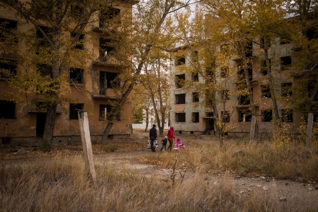 A family passes derelict housing blocks in the town of Kurchatov, © Phil Hatcher-Moore. Kazakhstan. Kurchatov was the headquarters of the Soviet nuclear project in Kazakhstan during the Cold War, and a quarter of the world's nuclear tests were conducted in the Semipalatinsk Test Site, just south of the town.