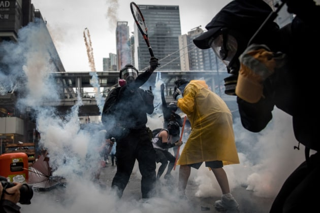 © Chris McGrath. HONG KONG - AUGUST 25: A protester uses a tennis racquet to hit back tear gas canisters during clashes with police after an anti-government rally in Tsuen Wan district on August 25, 2019 in Hong Kong, China. Pro-democracy protesters have continued rallies on the streets of Hong Kong against a controversial extradition bill since 9 June as the city plunged into crisis after waves of demonstrations and several violent clashes. Hong Kong's Chief Executive Carrie Lam apologized for introducing the bill and declared it