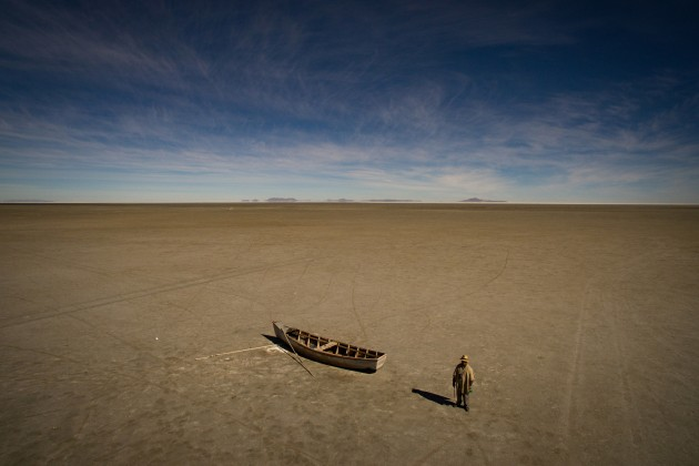 © Josh Haner/The New York Times. Felix Condori, 31, the mayor of Llapallapani, next to a boat in the dry bed that was once Bolivia's second-largest lake shown on May 1, 2016. Mr Condori, a former fisherman, now must travel to find construction jobs as a means to make money now that the lake that defined their culture and livelihood disappeared.