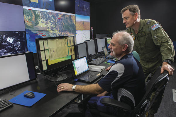 Mr Daryl Hopton from CAE Australia and Commanding Officer No 285 Squadron, Wing Commander Jason Baldock watch the progress of the training in the C-130J Simulator during Exercise Coalition Virtual Flag 16. Credit: Defence