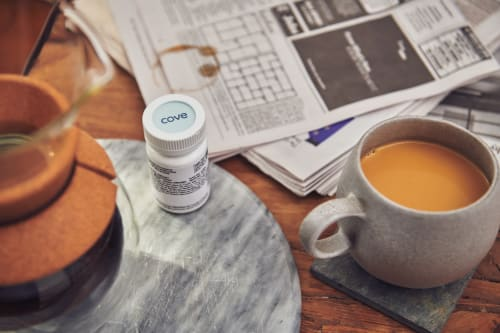 A Cove migraine medication bottle, situated between a chemex of coffee, a mug full of coffee, and a newspaper.
