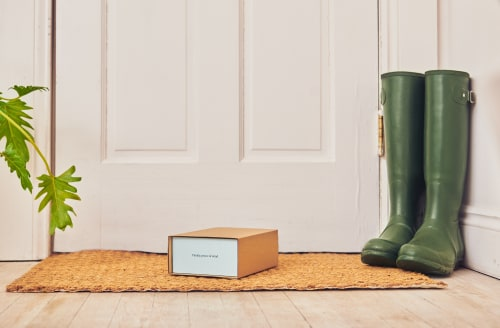 An image of a Cove migraine treatment box on a doormat, next to a pair of wellington boots and a plant.