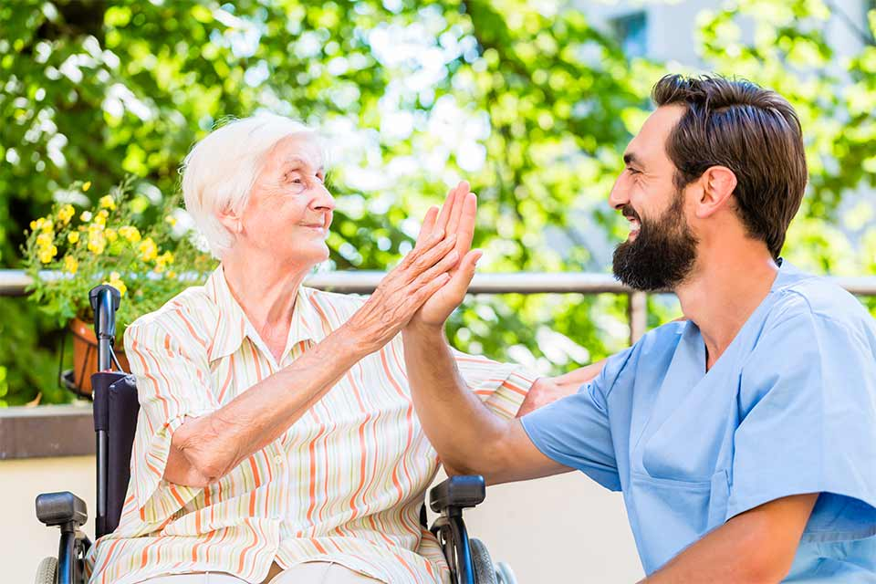 Elderly woman in memory care facility giving a high five to her caregiver