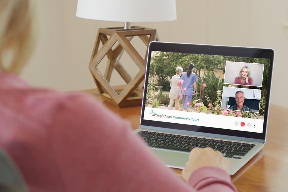Woman sitting at desk taking virtual senior living community tour on laptop