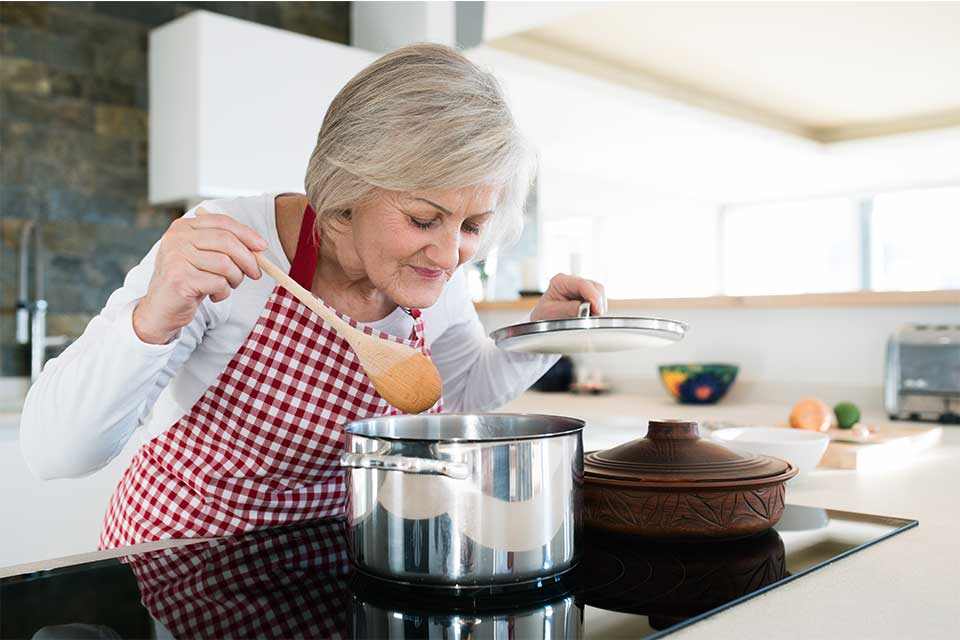 Elderly woman cooking pasta sauce on her stovetop.