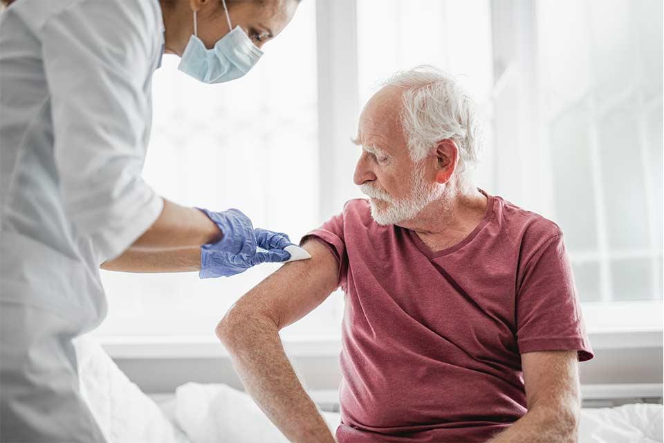 Elderly man in a red shirt receiving a coronavirus vaccine shot from a doctor.