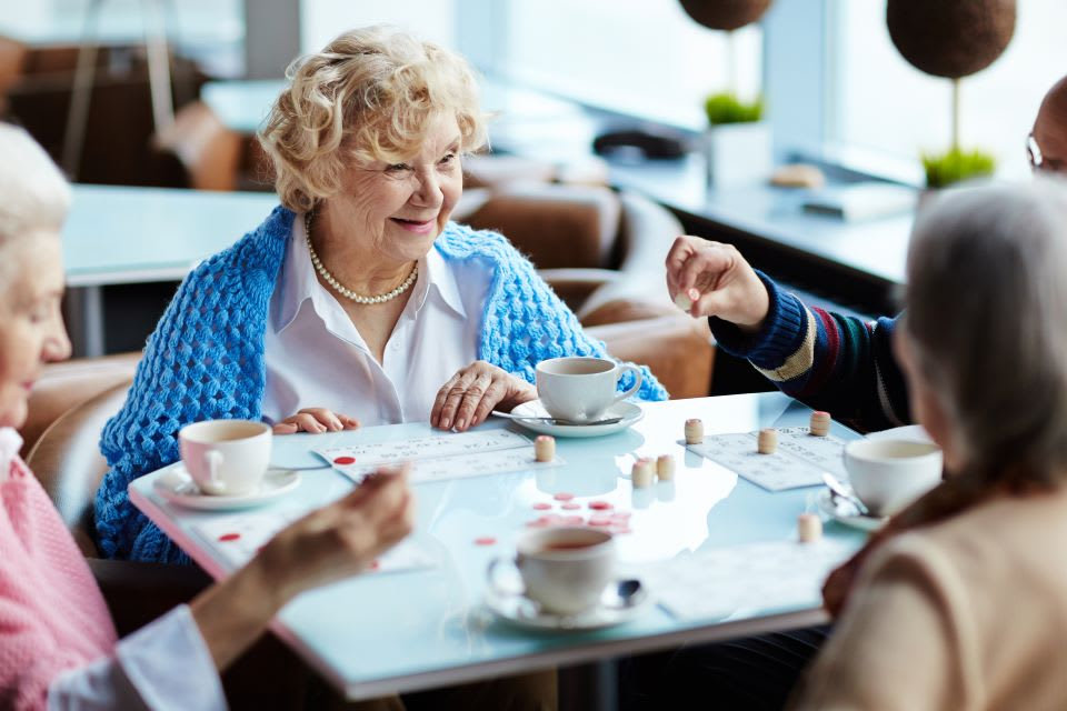 Happy elderly women drink tea and talk in the dining room of an assisted living facility.