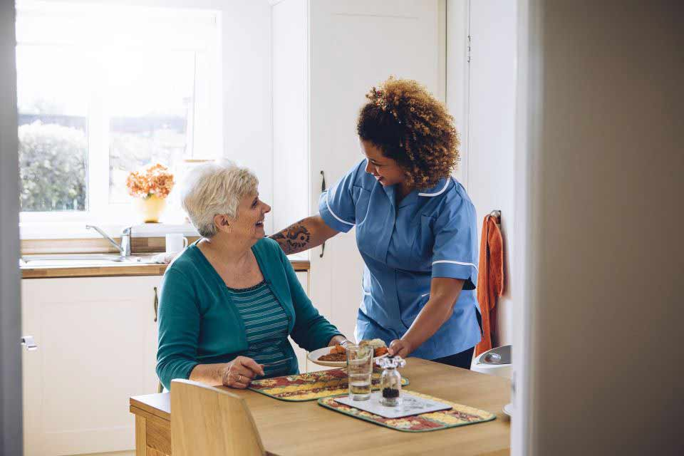 Assisted living nurse helping an elderly woman with her breakfast.
