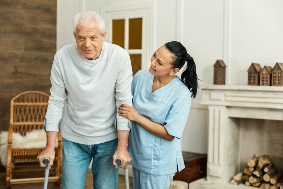 Caregiver helping elderly man walk at an assisted living facility.