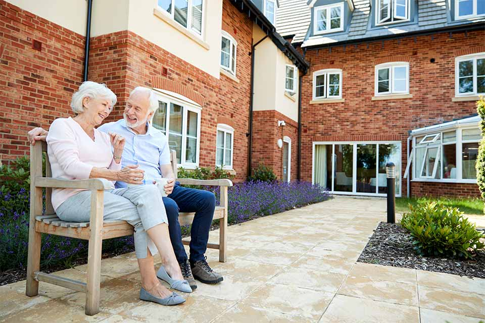 Elderly man and woman sitting in the courtyard of an assisted living facility that meets regulations