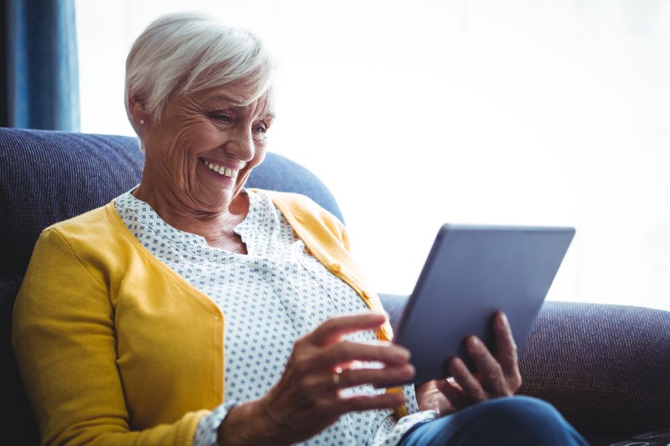 Elderly woman looks at a tablet.