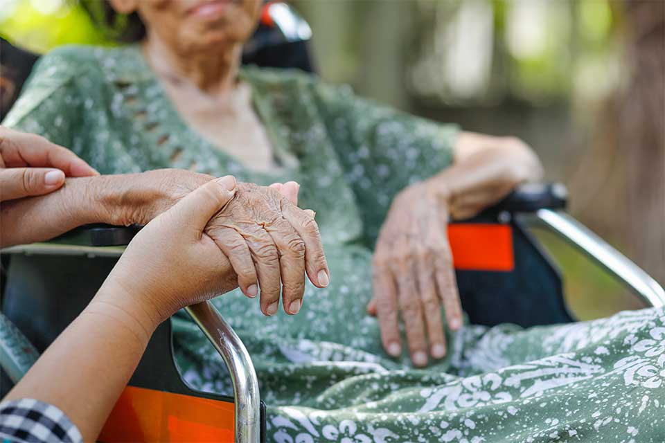Elderly woman in wheelchair holding hands with her caregiver