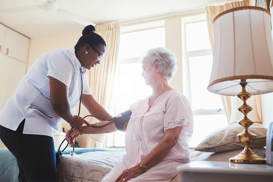 Elderly woman getting her blood pressure taken by a caregiver.