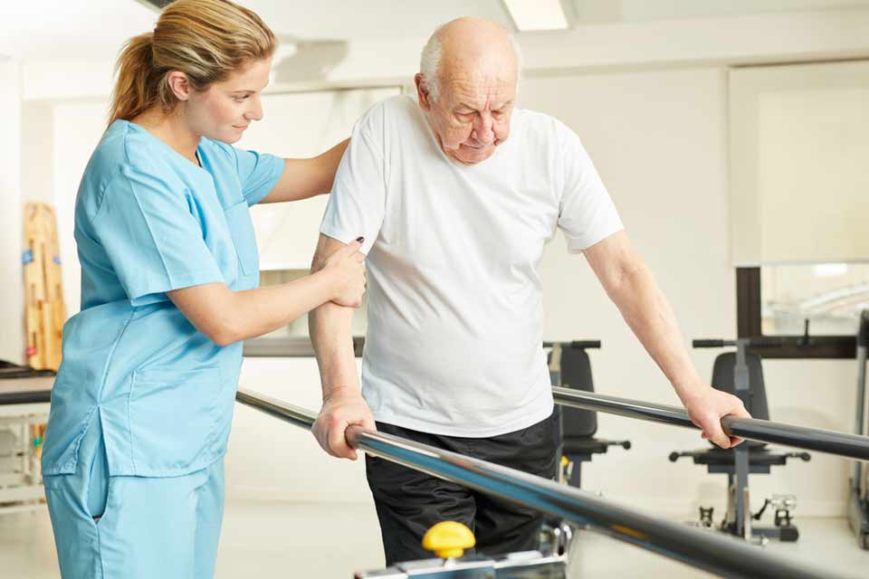 Nurse helping an elderly man with his ability to walk using bars.